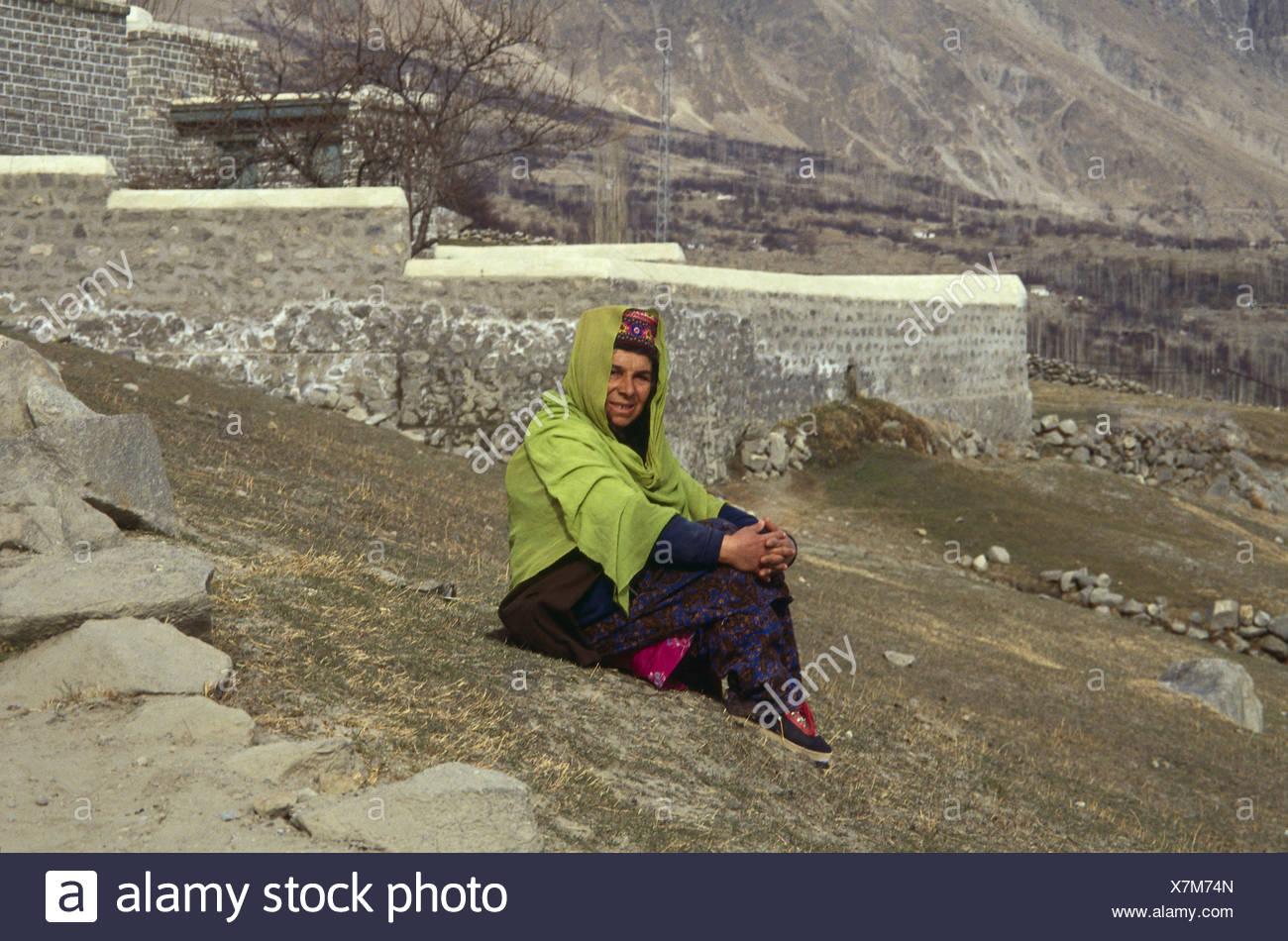 Pakistan,Karimabad,woman,Hunzukuc strain,sit,at the side,no model release,Asia,Karakorumgebirge,Karakorum,Hunzatal,Hunzukuc,tribe,locals,clothes,headgear,traditionally,outside,whole body, - Stock Image