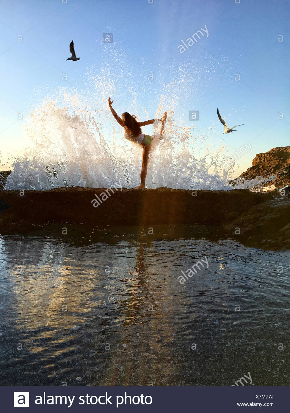 Woman in still bow yoga pose on cliffs at beach - Stock Image