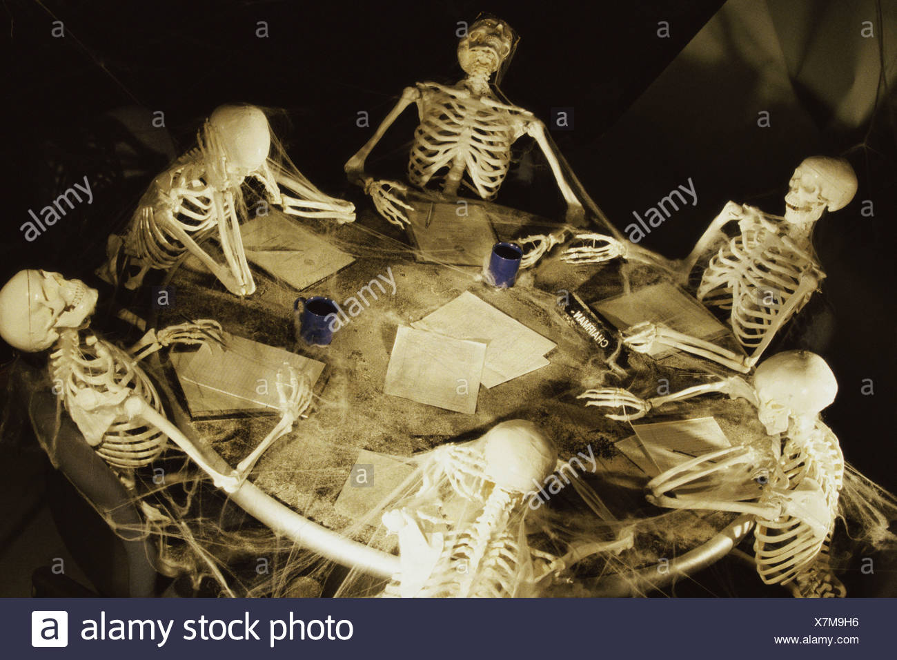 Human Skeletons Covered In Cobwebs At A Meeting Stock Photo