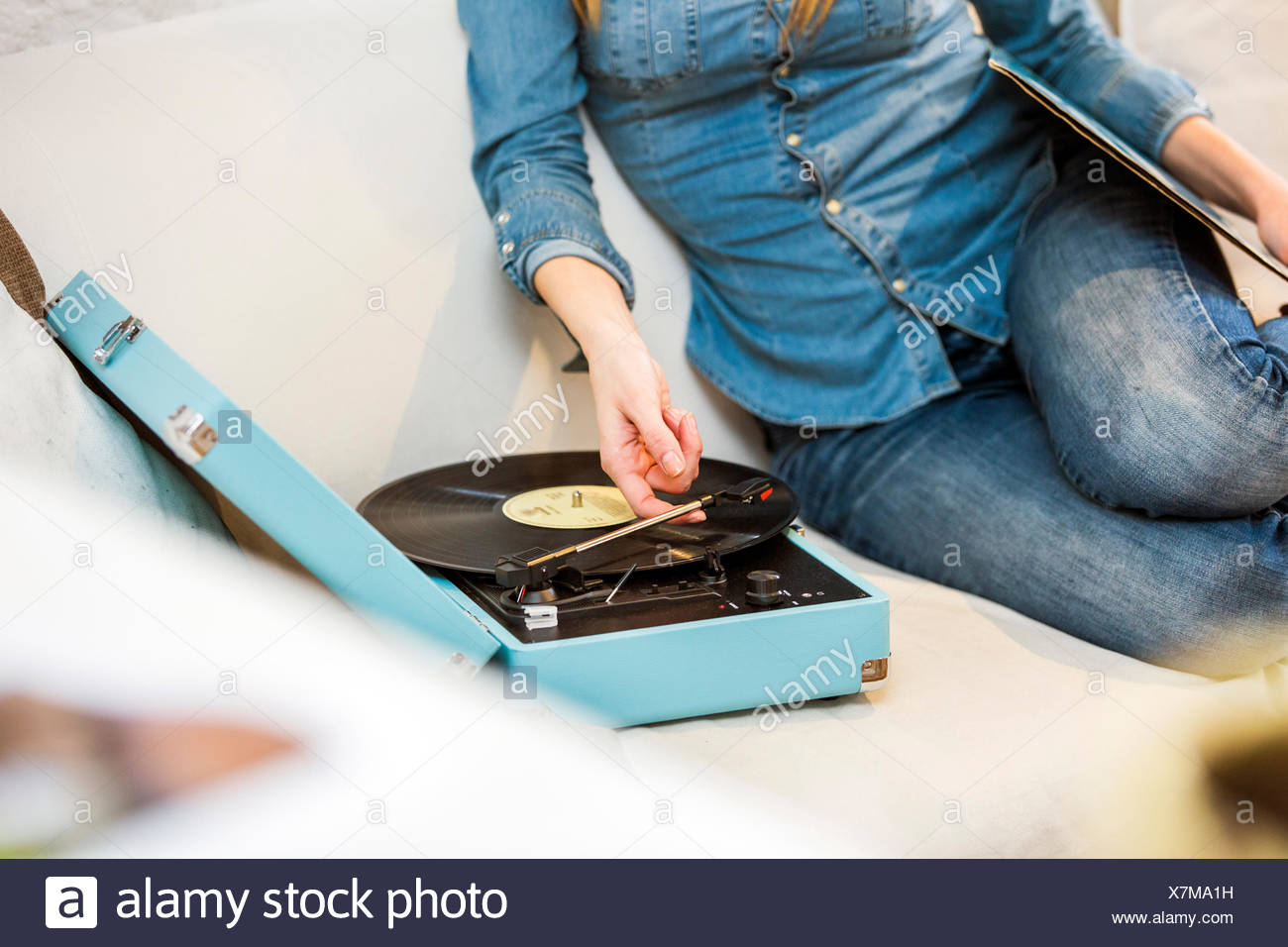 Cropped shot of young woman sitting on sofa listening to vintage record player - Stock Image