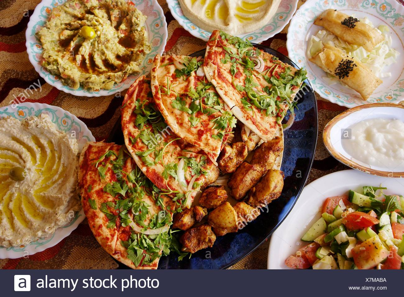 Food: different ´meze´ salads, ´hummus´ and more, with chiken ´kebab´ grill and bread, ´pizza´ style, Hama, Syria - Stock Image