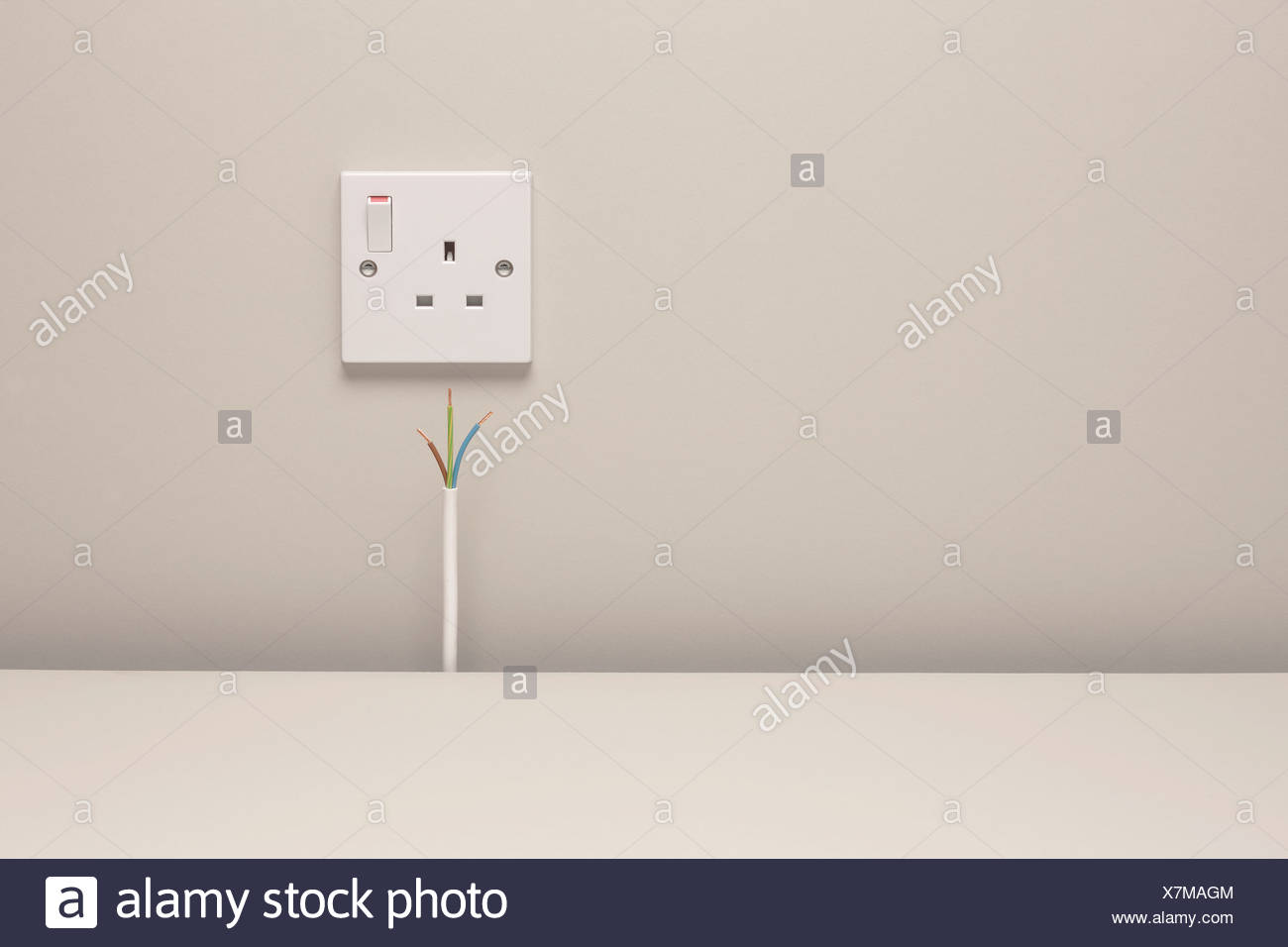 Bare wires by an electrical wall socket Stock Photo