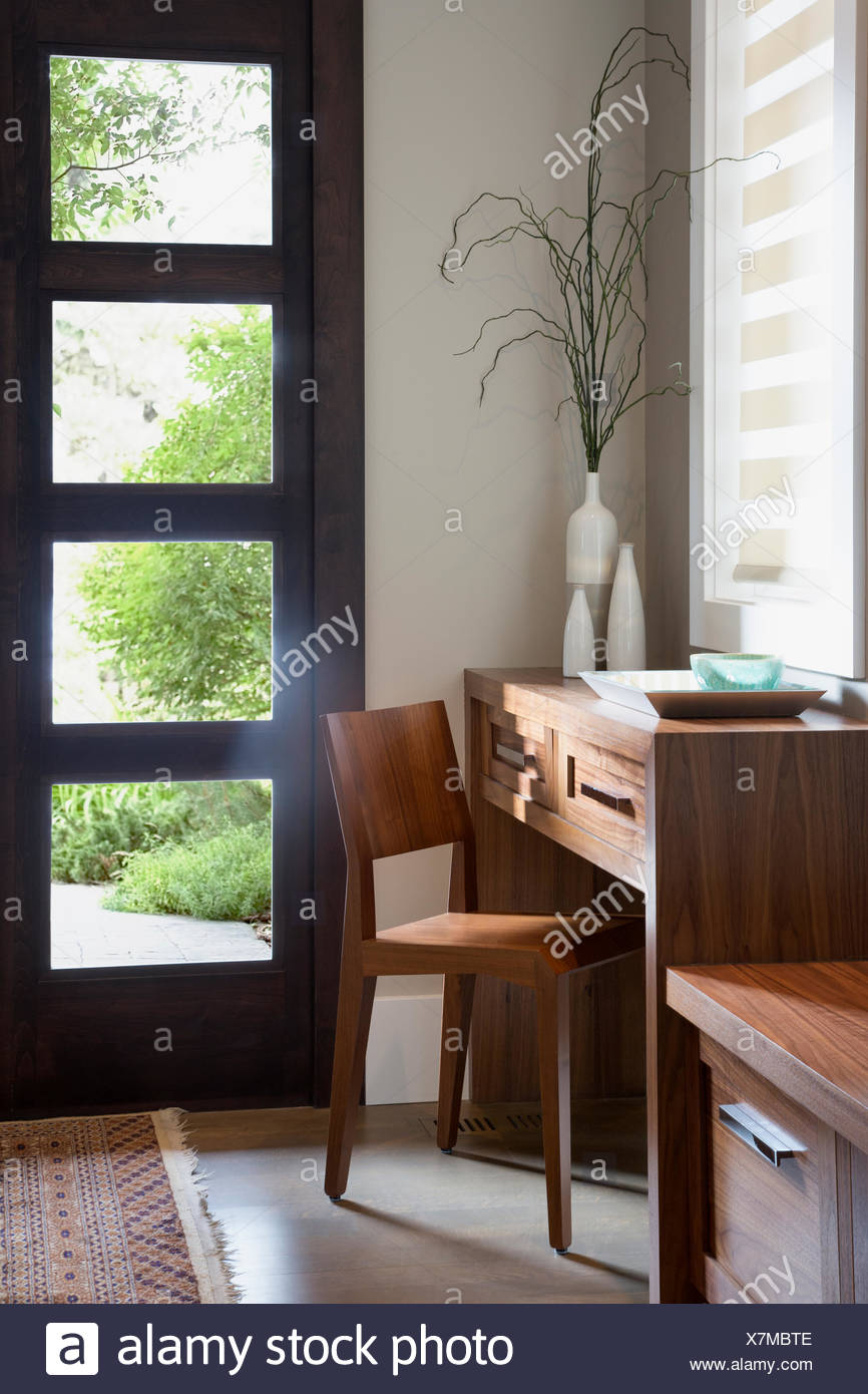 Wood desk and chair in sunny elegant corner - Stock Image