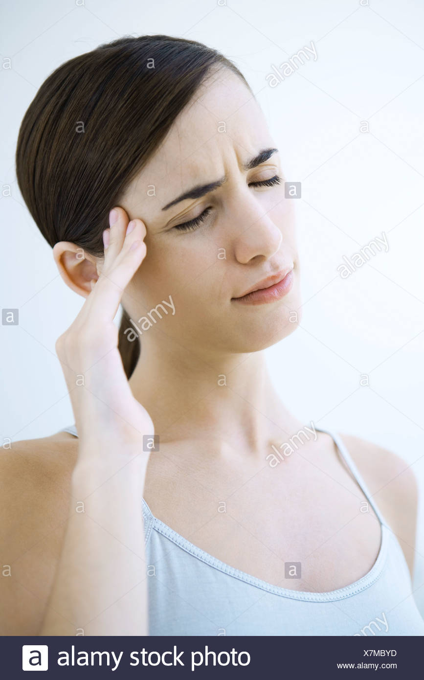 Woman massaging her temple and furrowing her brow, eyes closed - Stock Image