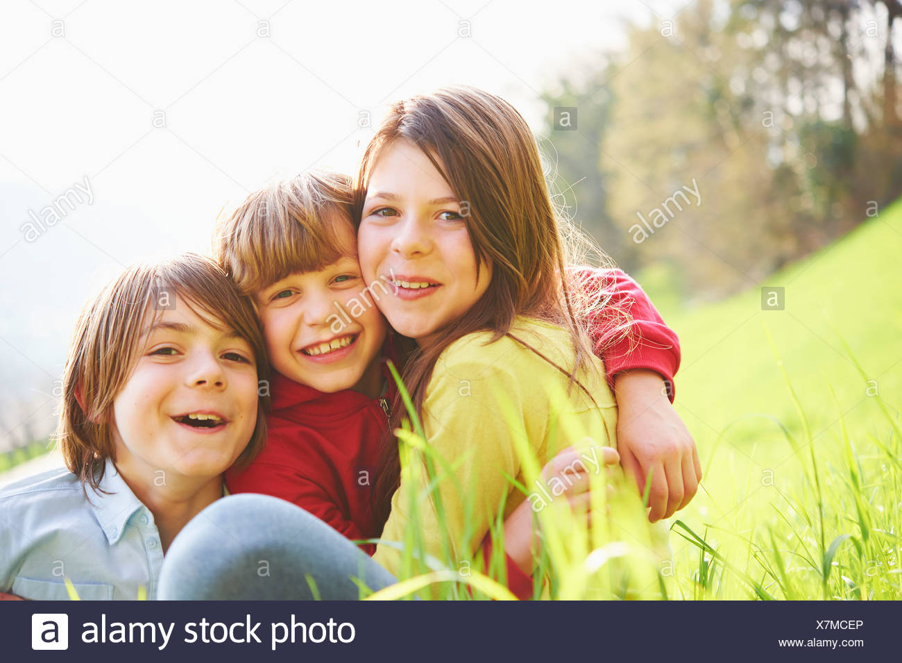 Sister and younger brothers sitting in grassy field - Stock Image