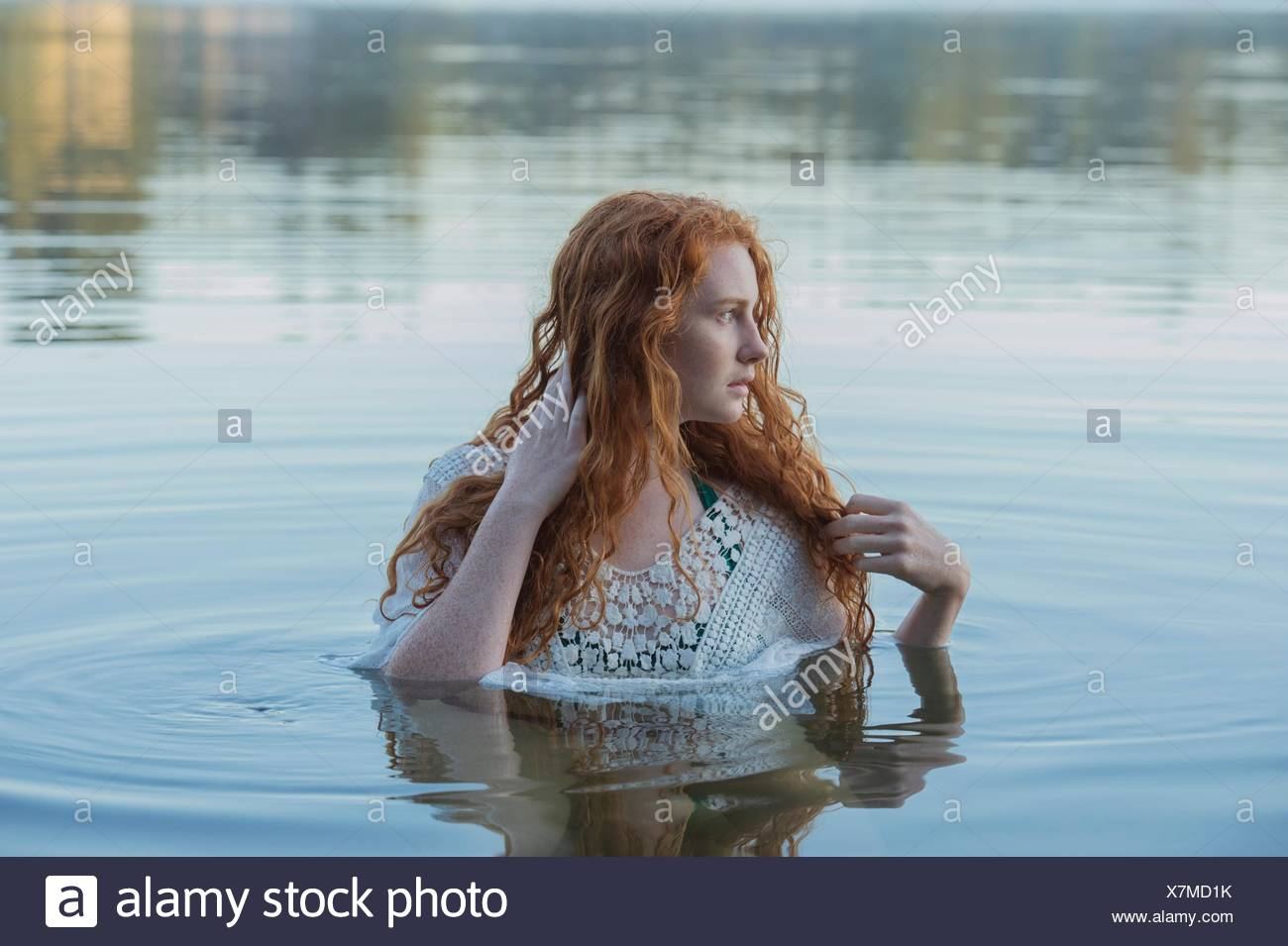 Head and shoulders of young woman with long red hair in lake looking sideways - Stock Image