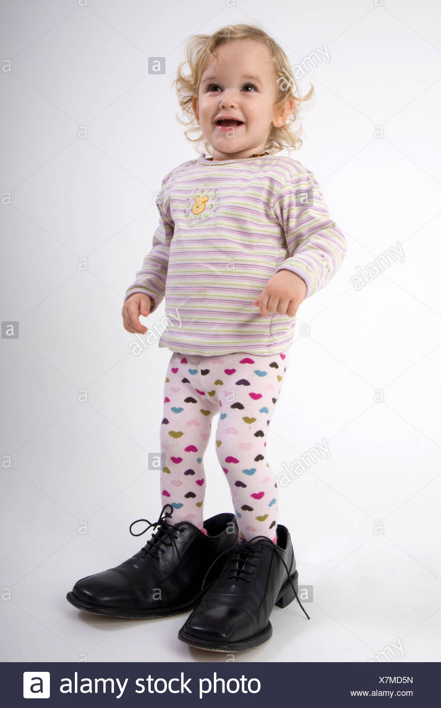 little girl in far too big black shoes