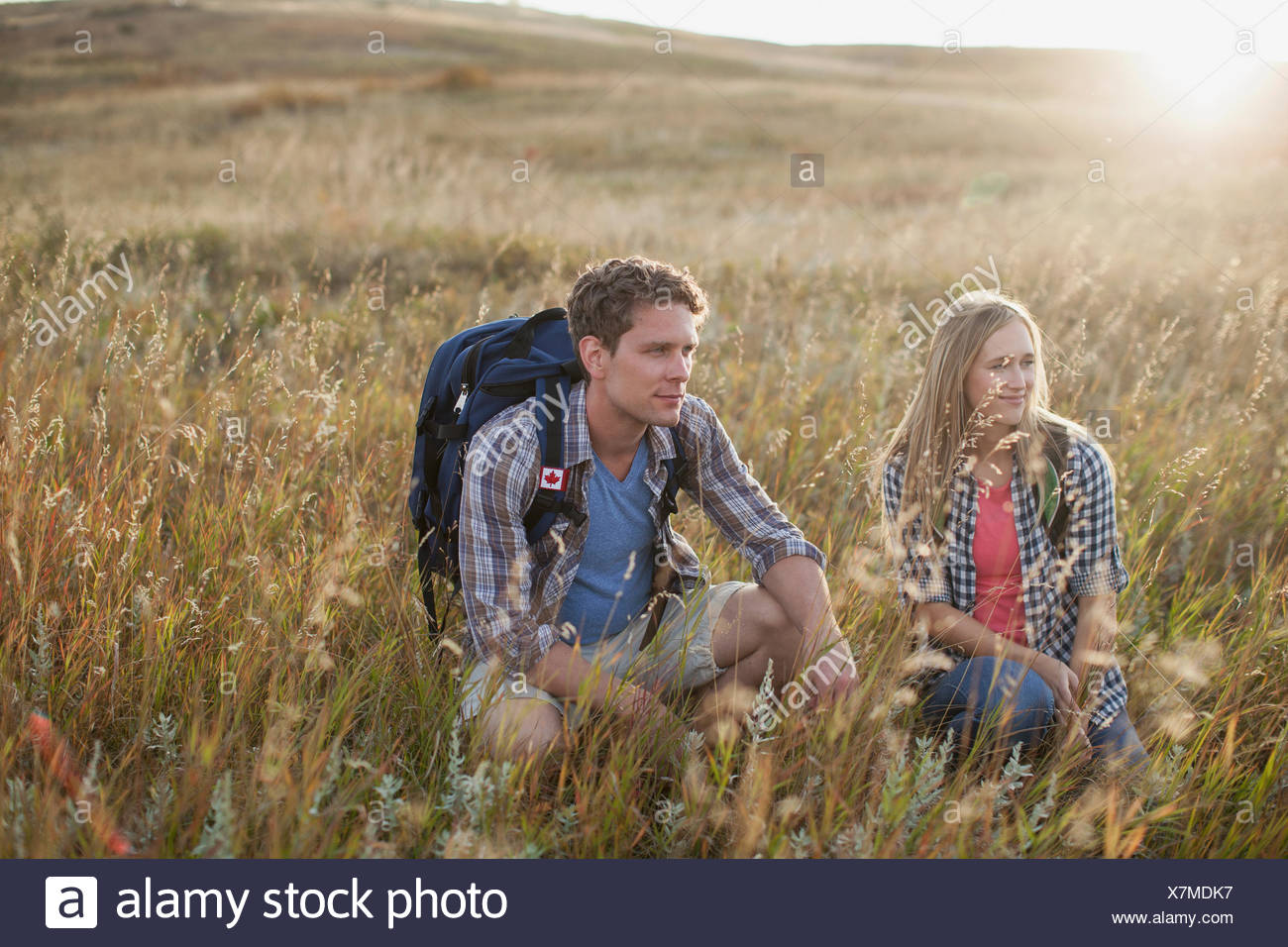 Couple crouching in grassy field. - Stock Image