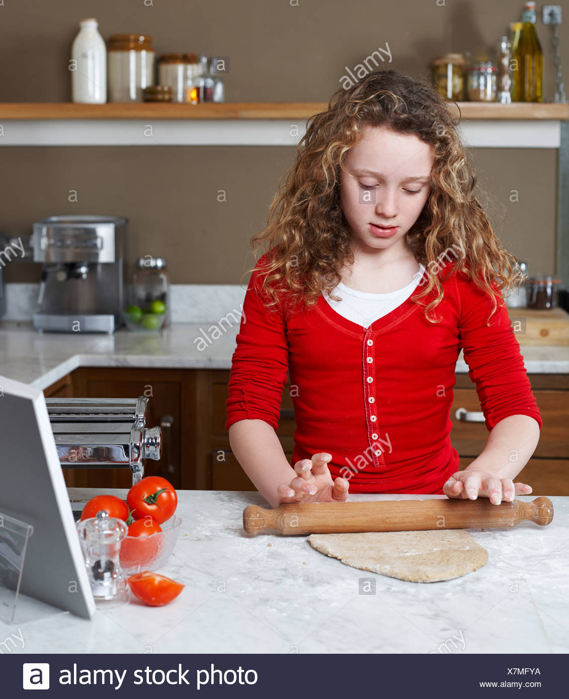 Girl rolling dough in kitchen - Stock Image