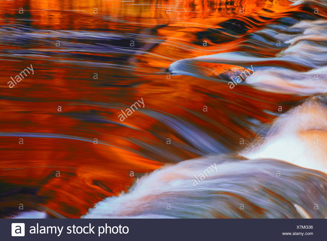 Mersey River reflections in autumn transformed into red via digital filter for a more interpretive effect at Kejimkujik National Park - Stock Image