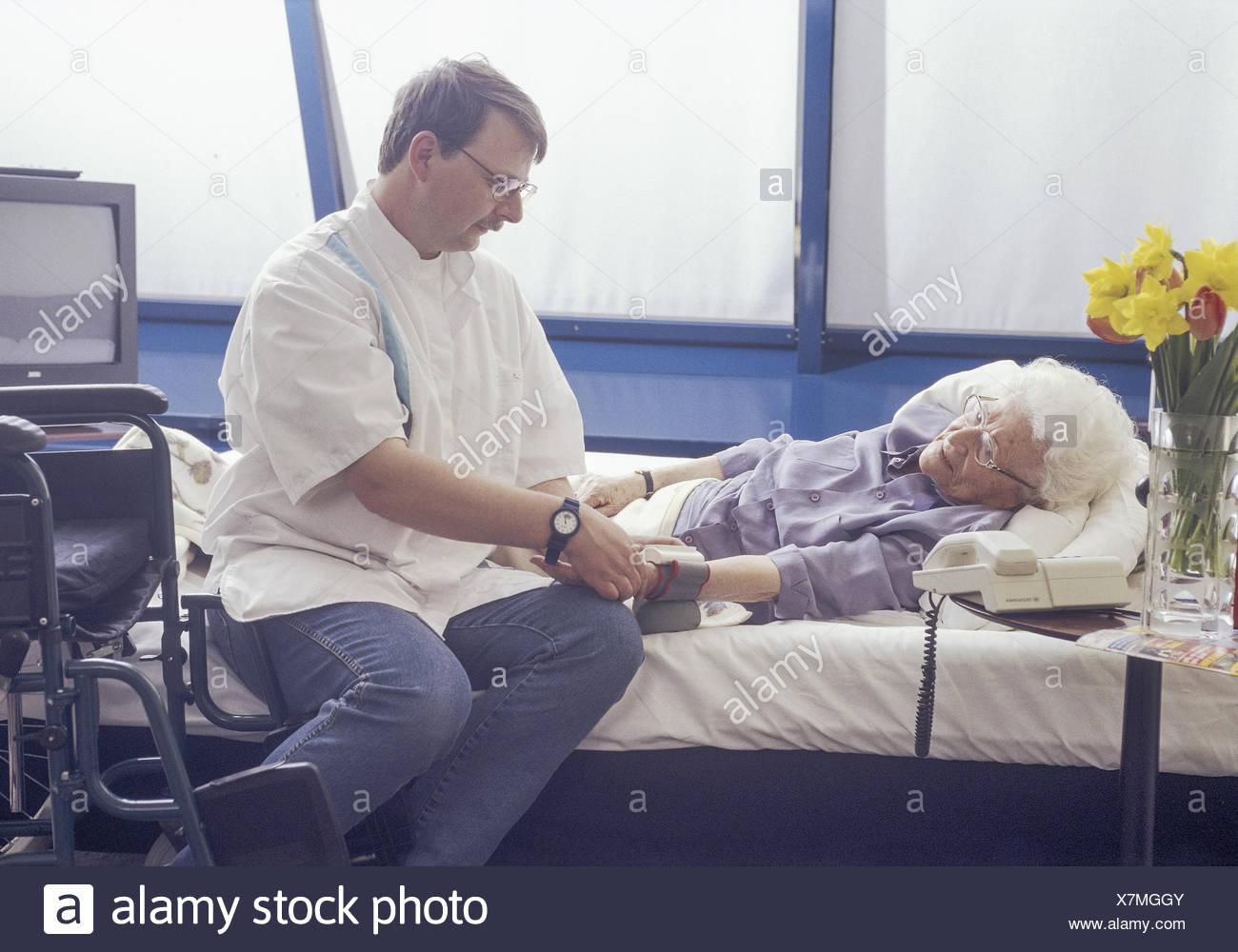 Altenpfleger beim Blutdruckmessen bei aelterer Seniorin am Bett (model-released) - Stock Image