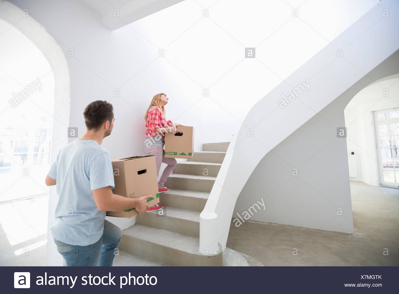 Couple Carrying Moving Boxes Up Stairs In New House Stock Photo