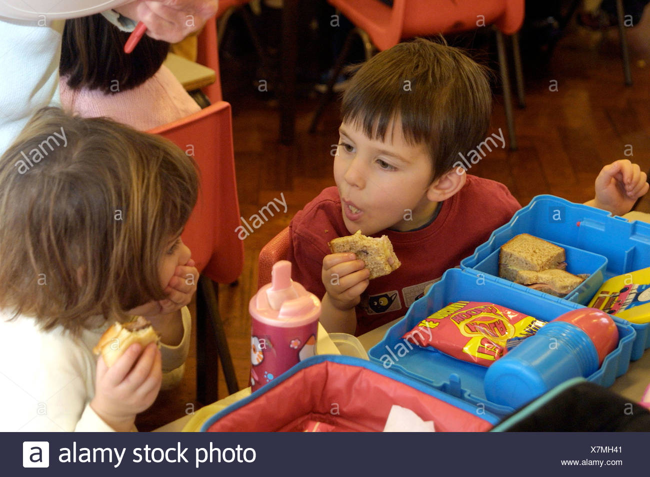 nursery school children eating packed lunch in cafeteria - Stock Image