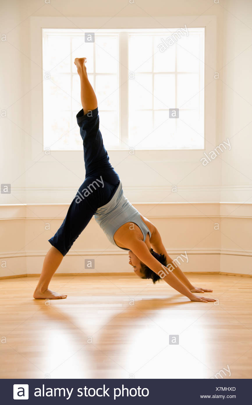 Young woman doing downward dog pose with one leg raised on wooden ...