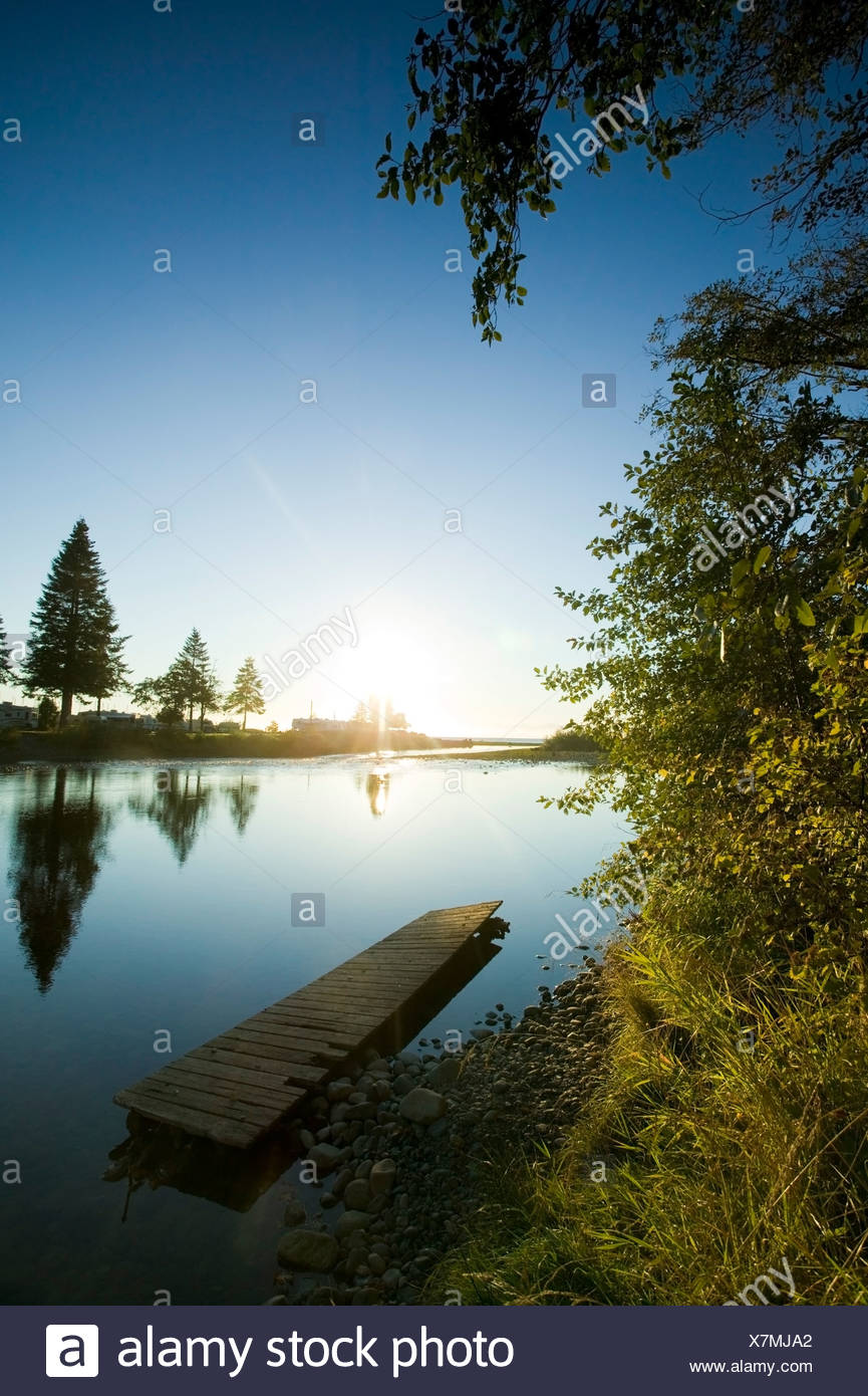 River at sunrise and an aging dock lend an air of tranquility to scene Oyster River Black Creek Vancouver Island British Columbi - Stock Image
