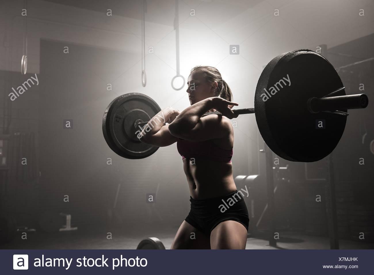 Young woman lifting barbell - Stock Image