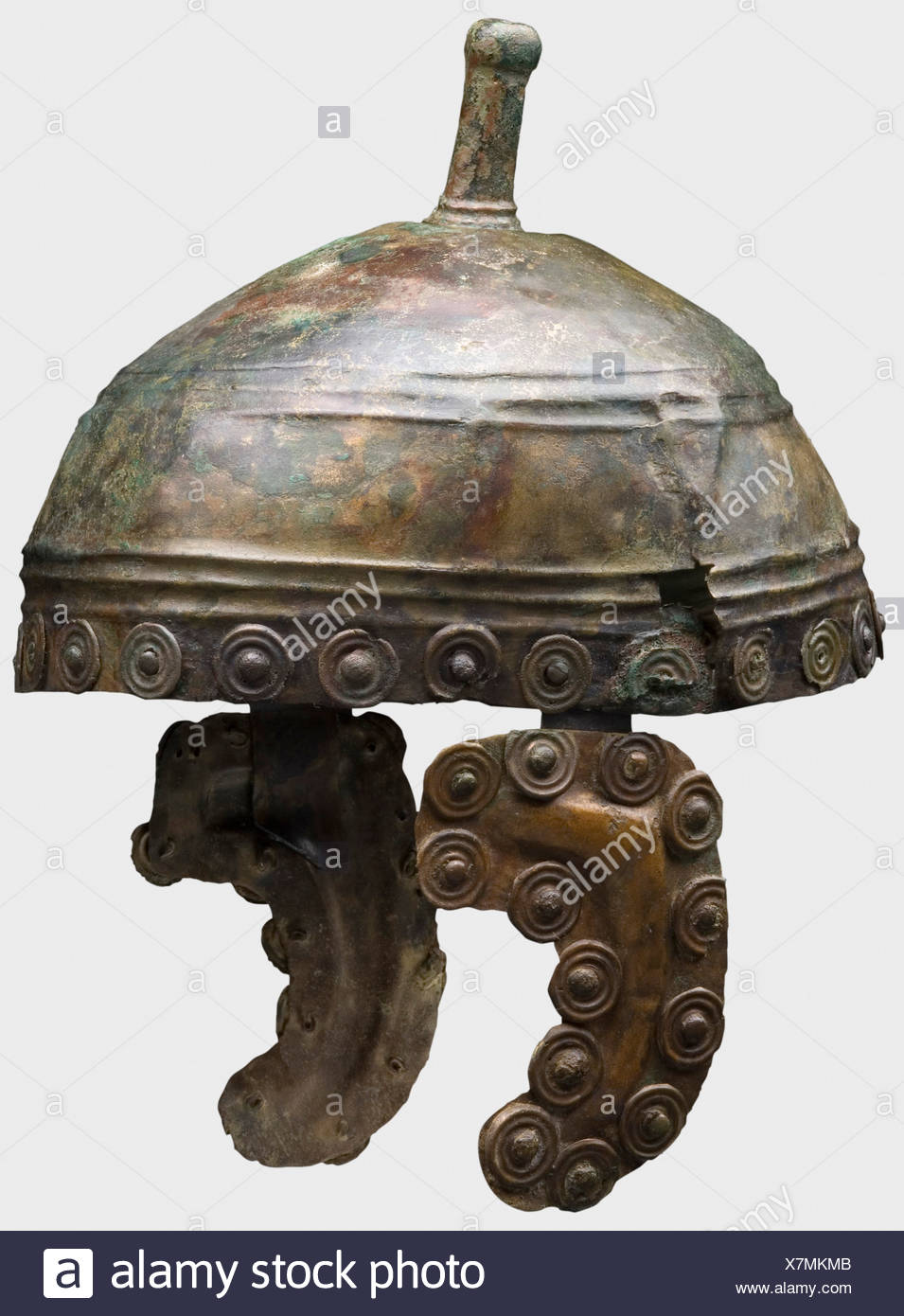 A Bronze Age helmet, 13th/12th century B.C. Shallow bronze skull with two bands of triple ridges and a cast-on helmet knob with a cylindrical opening for the helmet crest. Curved cheek pieces, formerly attached to the helmet lining. Decorative discs riveted around the perimeter of the helmet and the cheekpieces. Total height 16.5 cm. Weight 483 g. In addition decorative mountings, two bracelets, and an arrow head. The metal is well-preserved with a green patina in places, and organic and dirt residue. Slightly deformed. Cracked on one side. The interior stabili, Additional-Rights-Clearances-NA - Stock Image