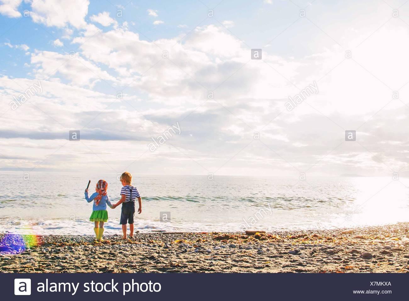 Boy (2-3) holding girl's (2-3) hand on beach - Stock Image