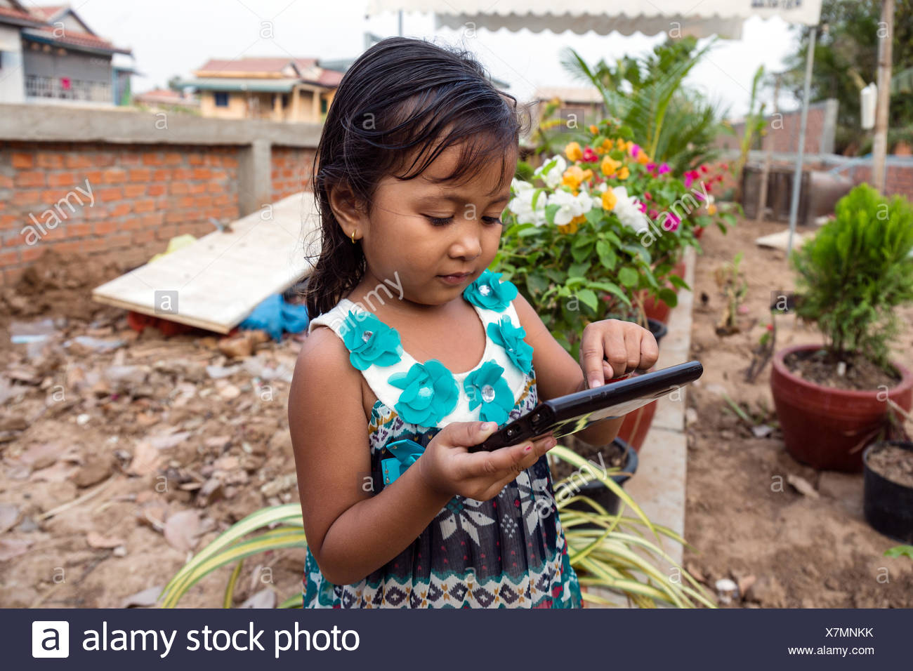 Little girl playing with a tablet computer, Phnom Penh, Cambodia - Stock Image