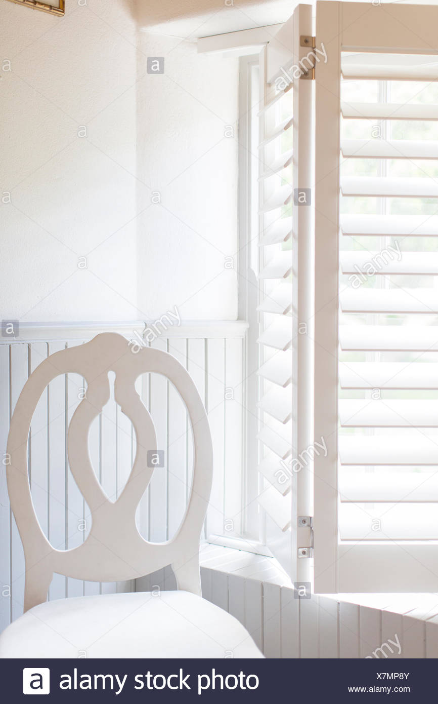 Chair by window with wooden blinds - Stock Image