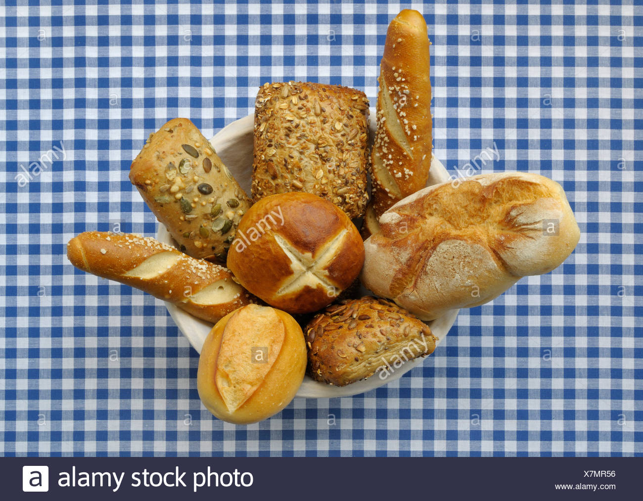 Bread basket filled with different kinds of rolls and lye rolls on a blue and white checked table cloth - Stock Image
