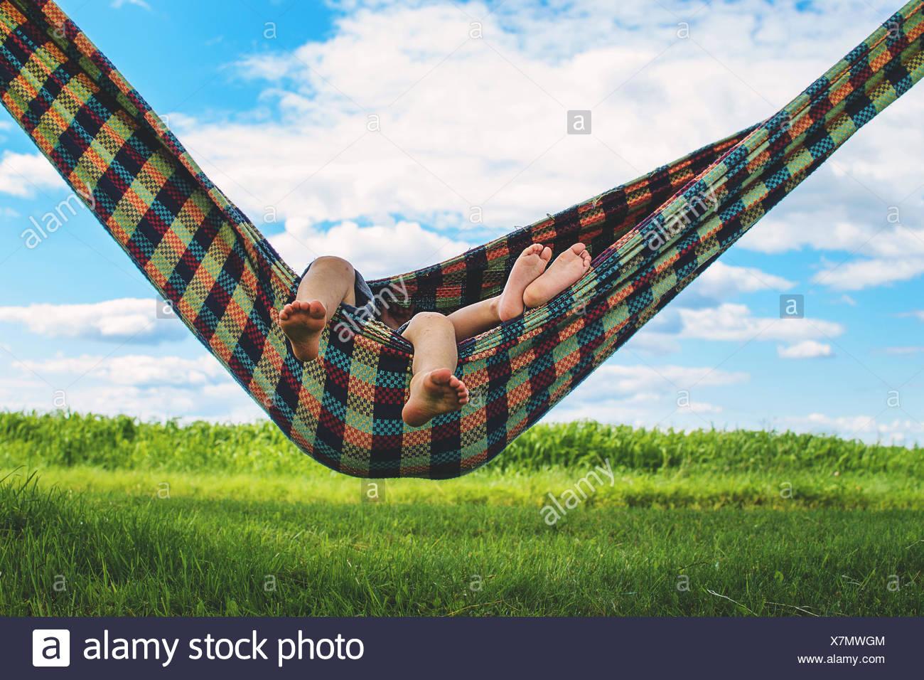 Children (2-3) relaxing in hammock - Stock Image