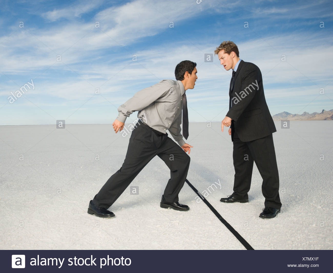 Businessmen on opposite sides of line, Salt Flats, Utah, United States - Stock Image