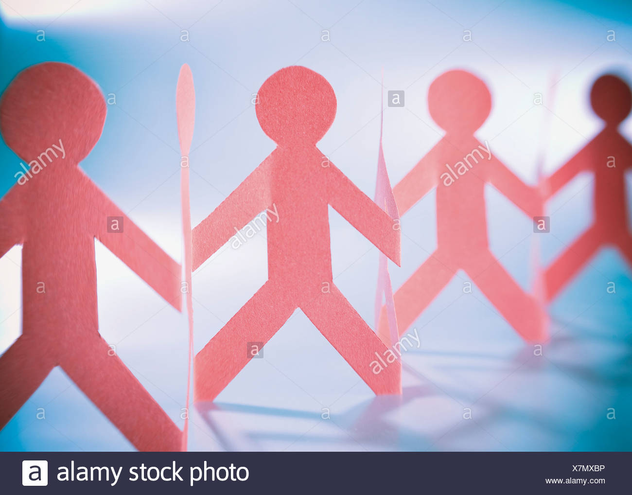 Red paper garland of people, close-up - Stock Image