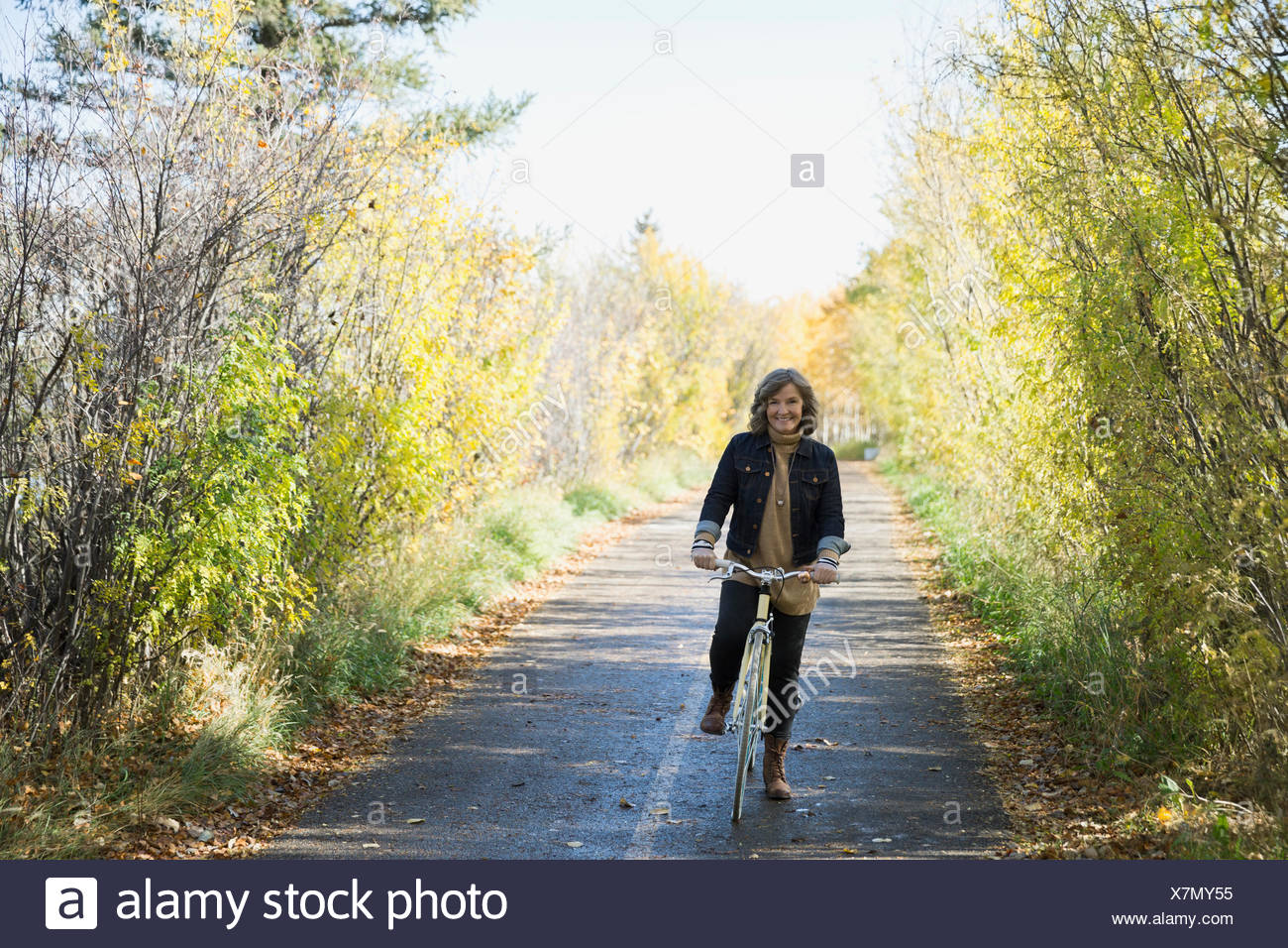 Woman bike riding on autumn path in park - Stock Image