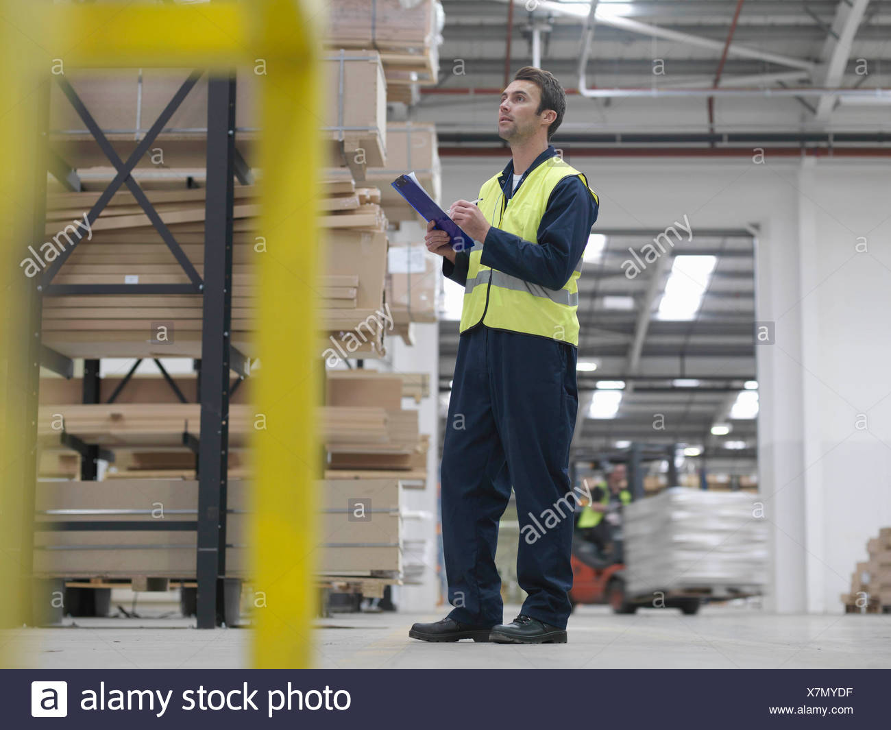 Worker With Clipboard In Warehouse - Stock Image