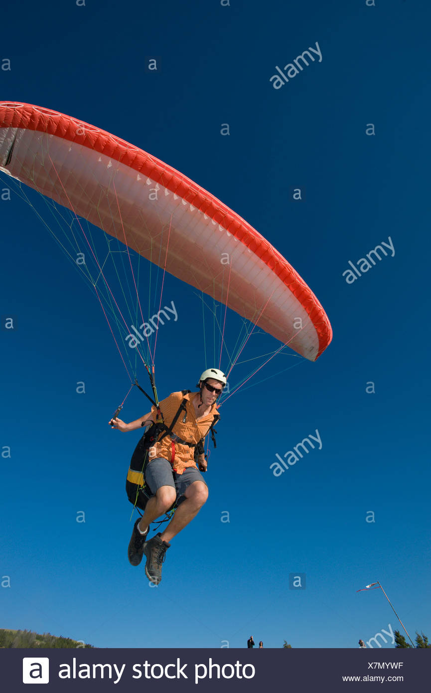 A paraglider lifts off the ground to begin his flight. - Stock Image