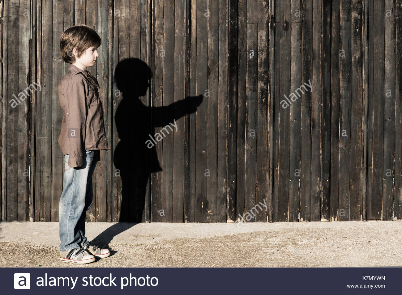 Boy standing next to a wooden fence with alter ego shadow Stock Photo