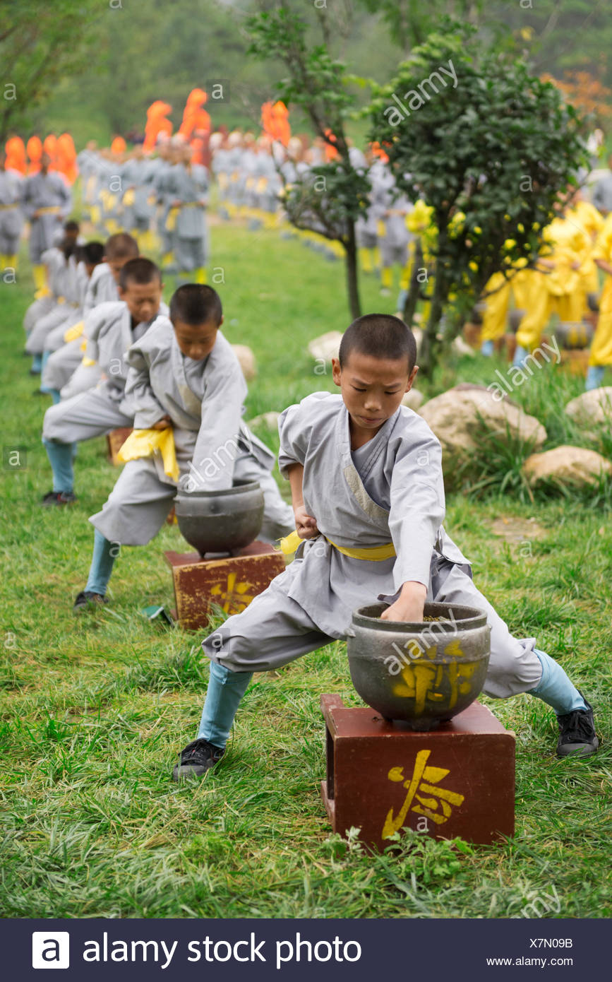 Young Shaolin Kung Fu students conditioning their fists by punching green beans in pots at the opening ceremony of Zhengzhou - Stock Image