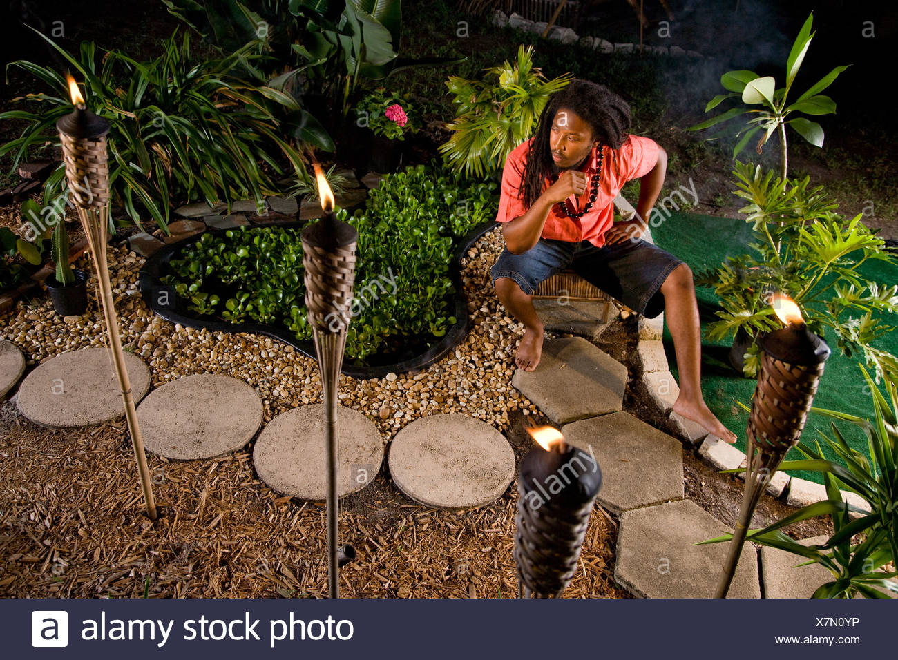 Young Jamaican man with dreadlocks sitting in tropical garden - Stock Image