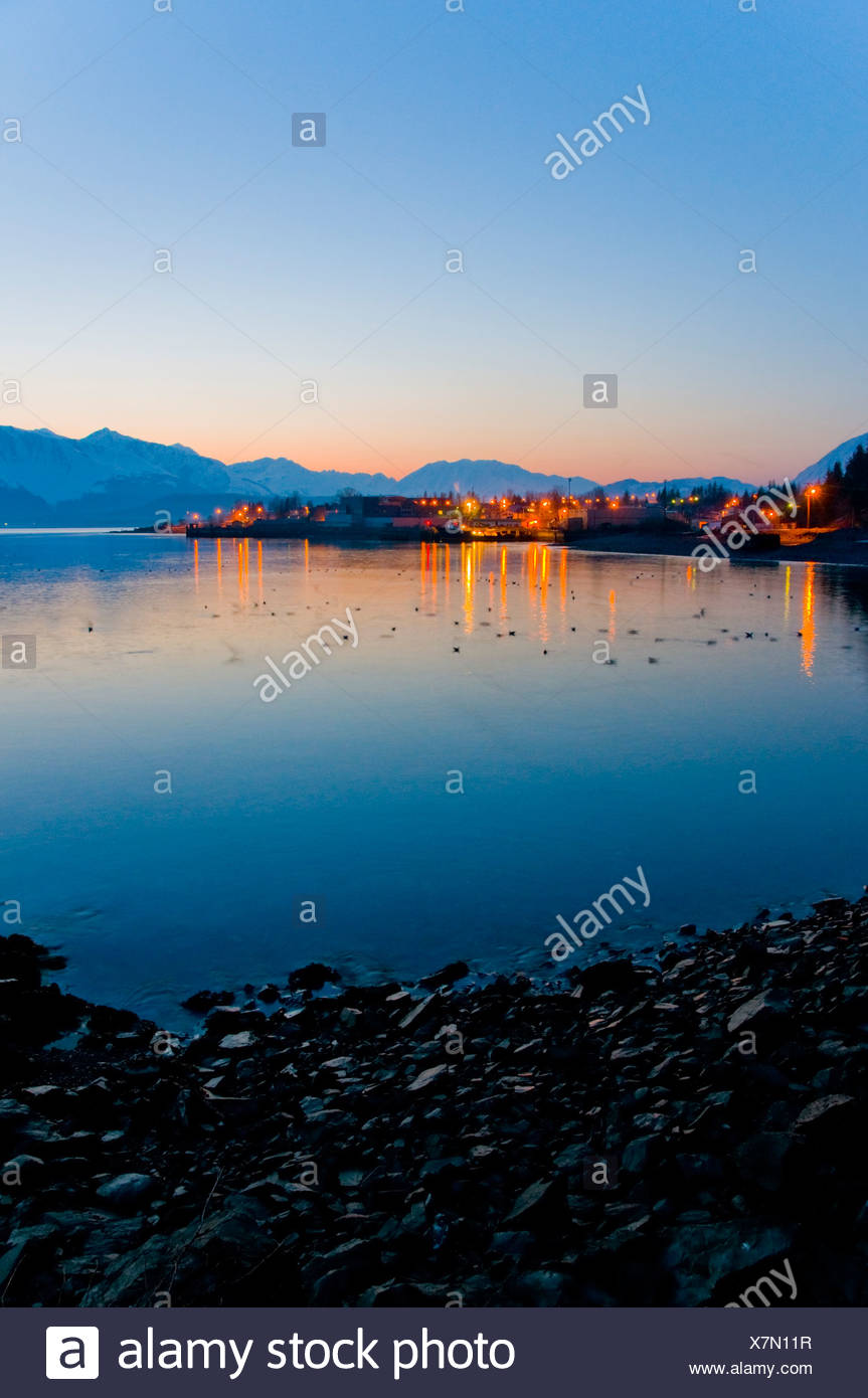 Sunrise over the lights of  Seward and  Resurrection Bay with the Kenai Mountains in the background, Alaska - Stock Image