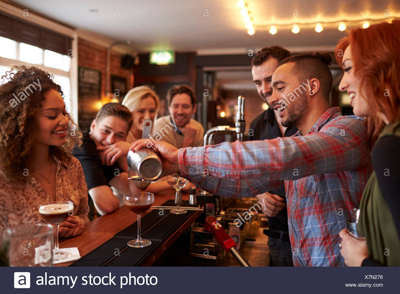 Man Learning How To Mix Cocktail At Lesson In Bar Stock Photo