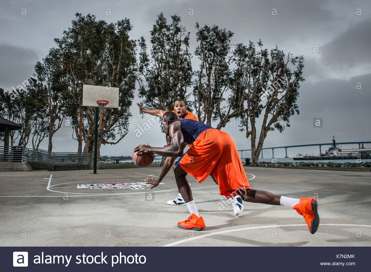 Young men playing basketball on court - Stock Image
