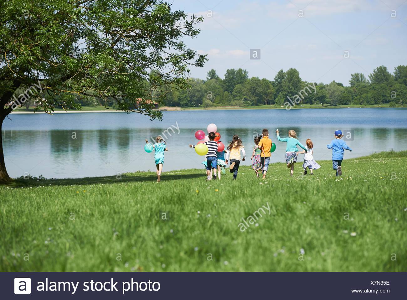 Rear view of children running in park with balloons, Lake Karlsfeld, Munich, Bavaria, Germany - Stock Image