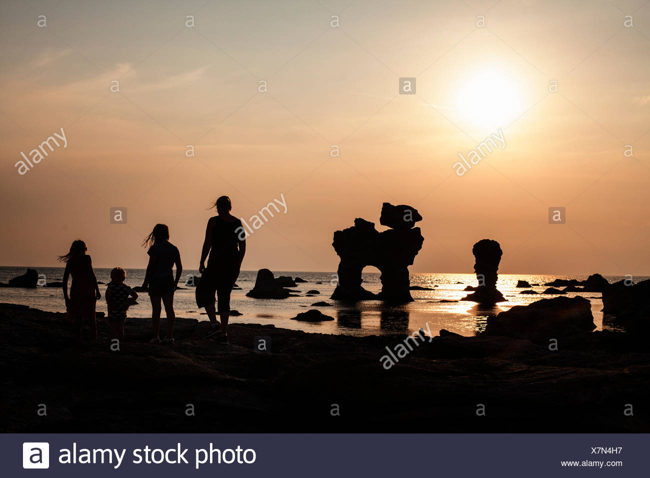 Sweden, Gotland, Faro, Gamle hamn, Silhouette of mother and children (2-3, 8-9, 10-11) on beach at sunset Stock Photo