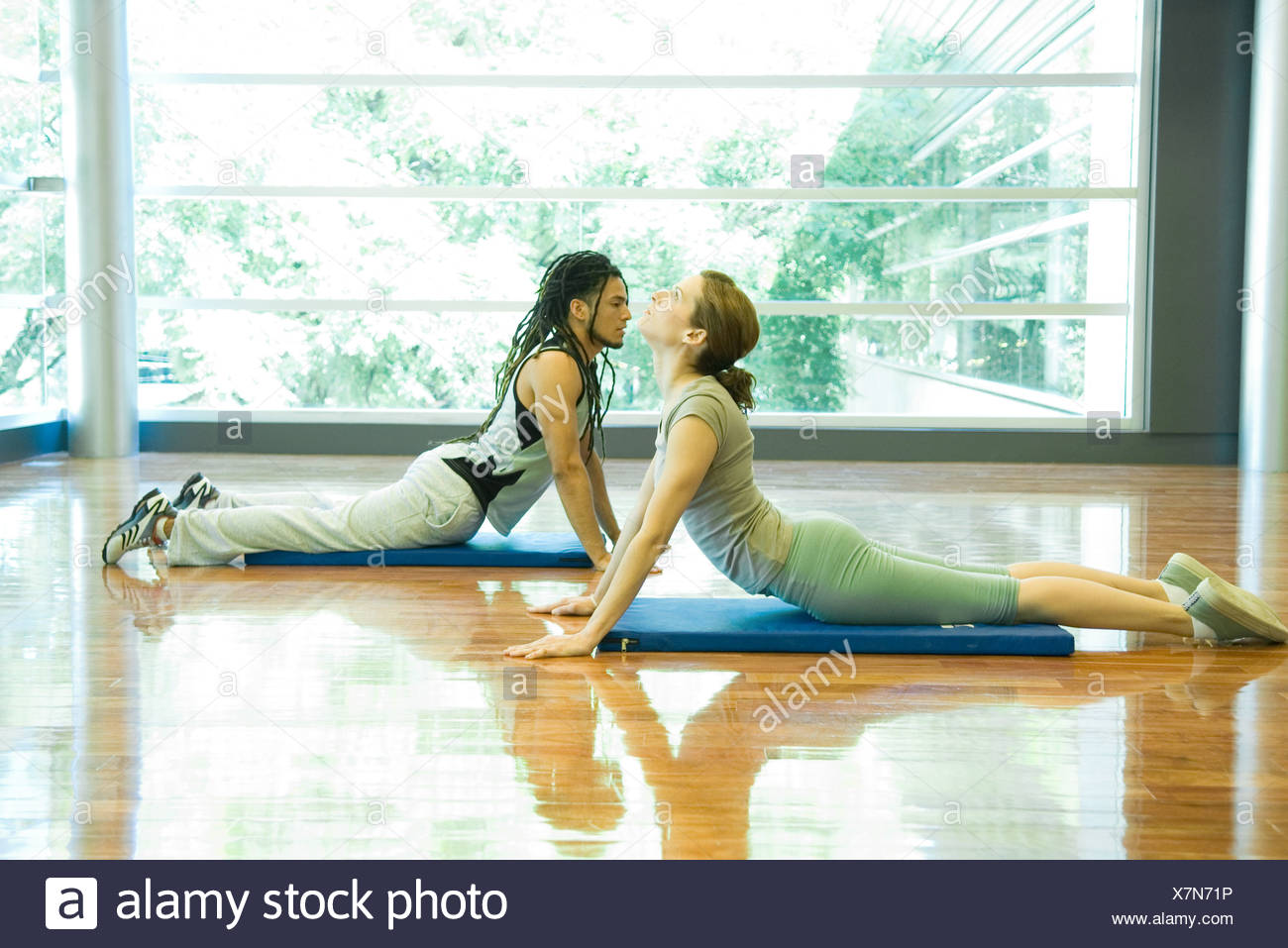 Two young adults doing cobra pose in yoga studio - Stock Image