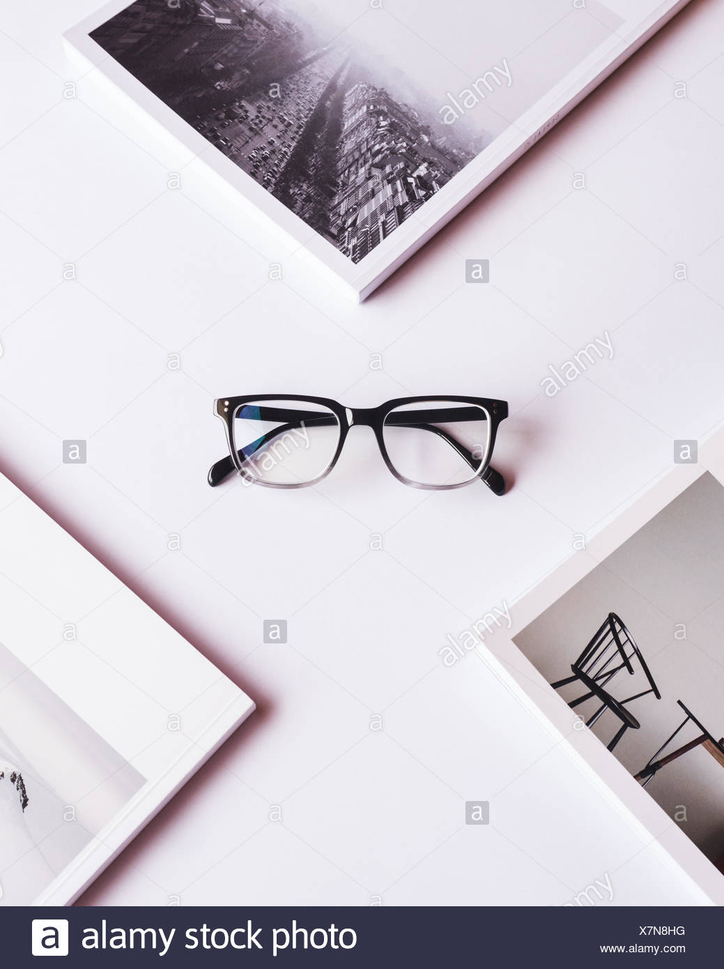 High Angle View Of Eyeglasses With Photographs On Table - Stock Image