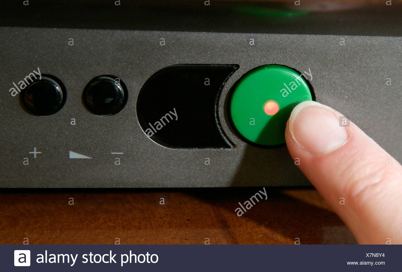 Finger pushing a standby button on a television, Regensburg, Bavaria, Germany, Europe - Stock Image