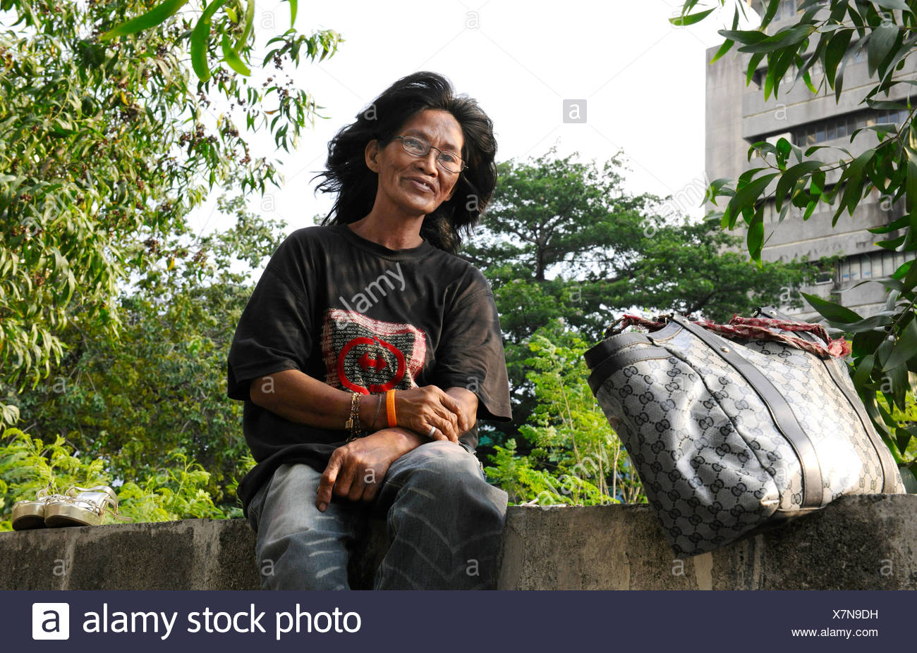 Unemployed woman sitting on a wall, Manila, Philippines, Southeast Asia - Stock Image