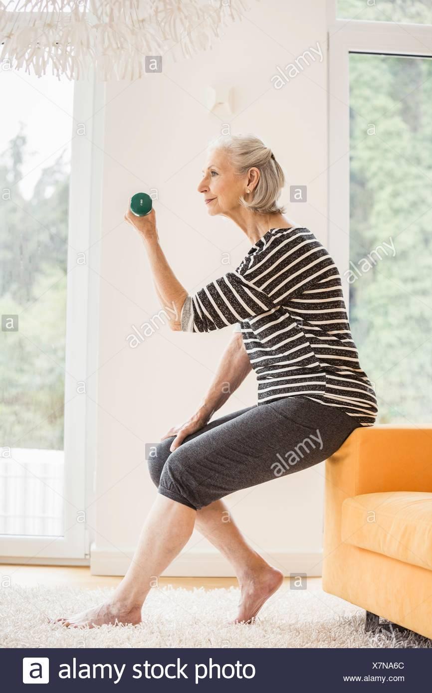 Senior woman sitting on sofa exercising with dumbbell - Stock Image