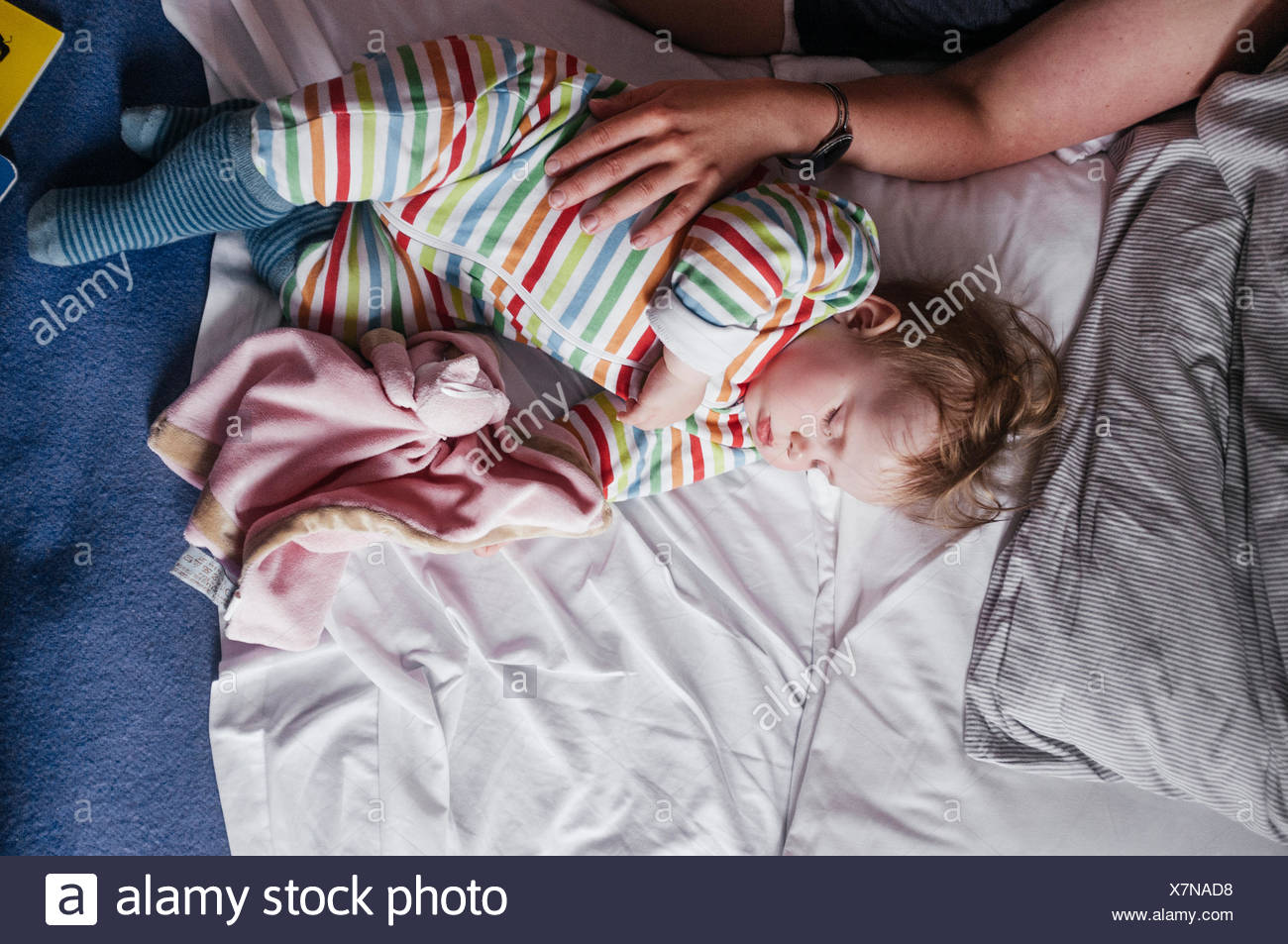 Cropped image of woman touching baby girl on bed - Stock Image