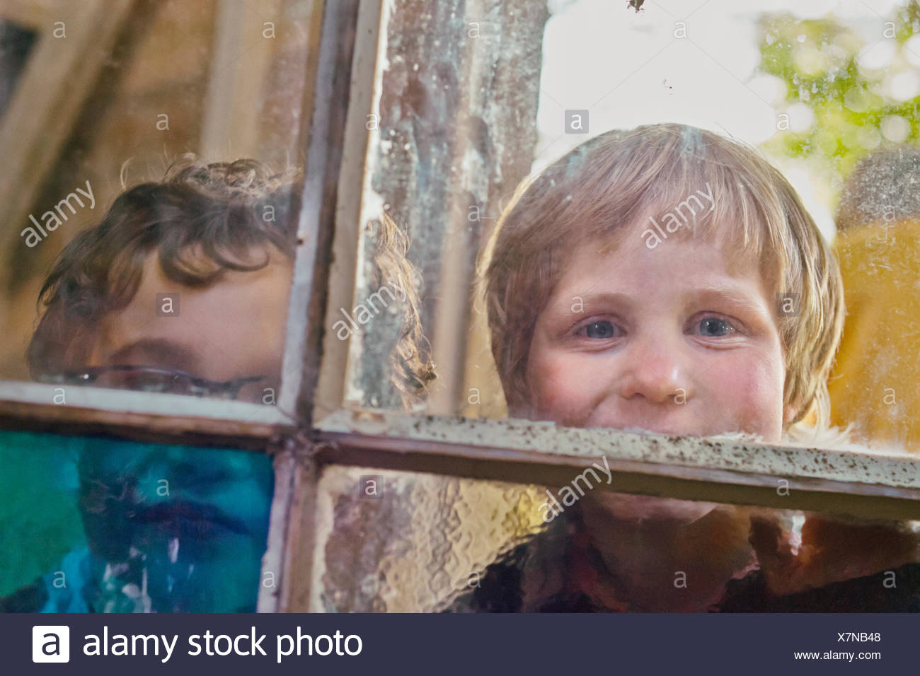 Portrait of two boys looking through hut window Stock Photo