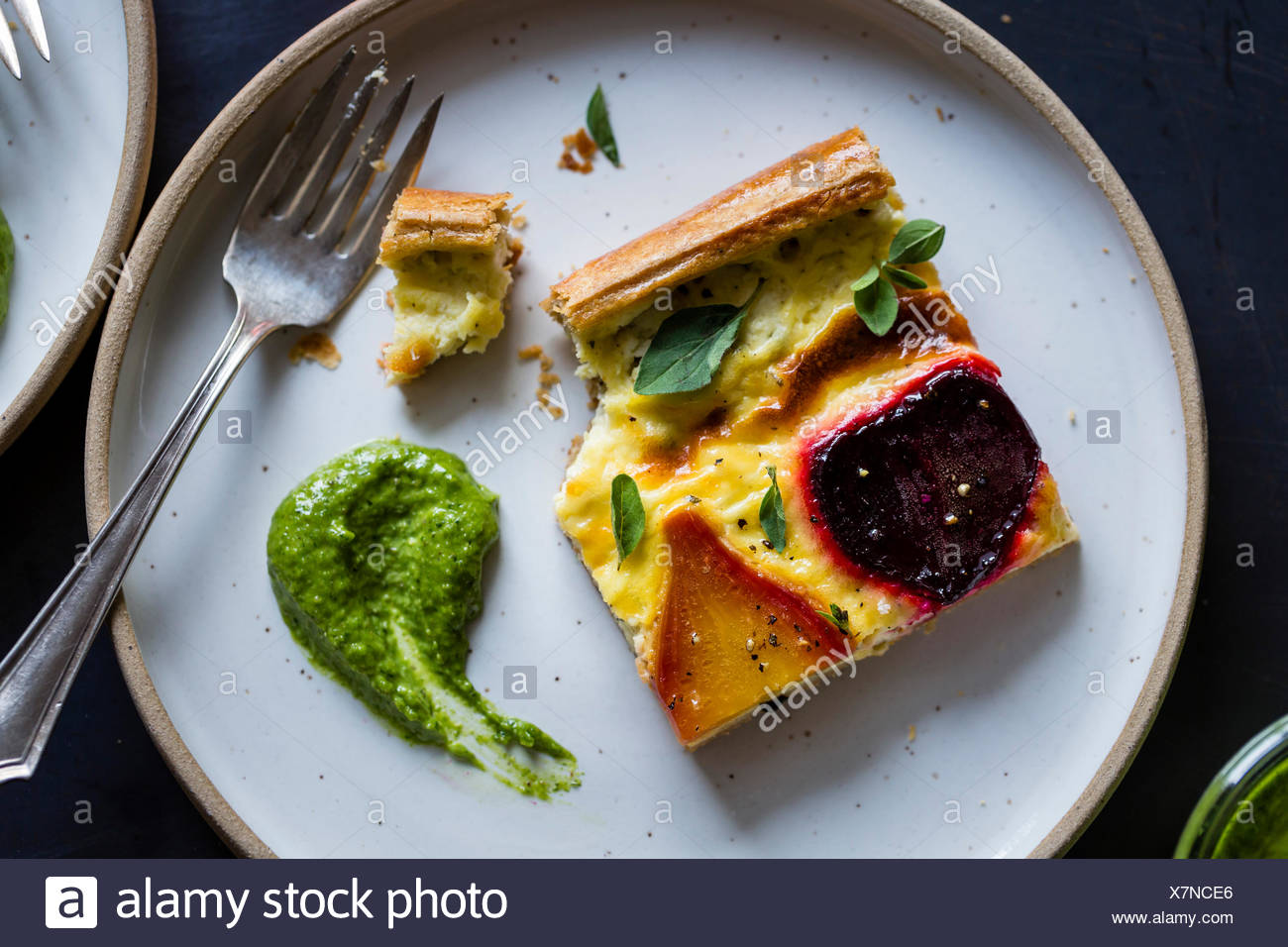 Beetroot ricotta cheese tart with beet greens pesto. Stock Photo