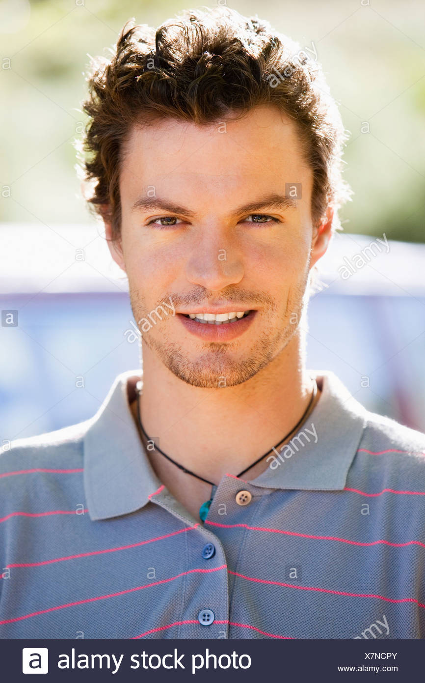 Young man wearing striped purple polo shirt smiling front view close up portrait - Stock Image