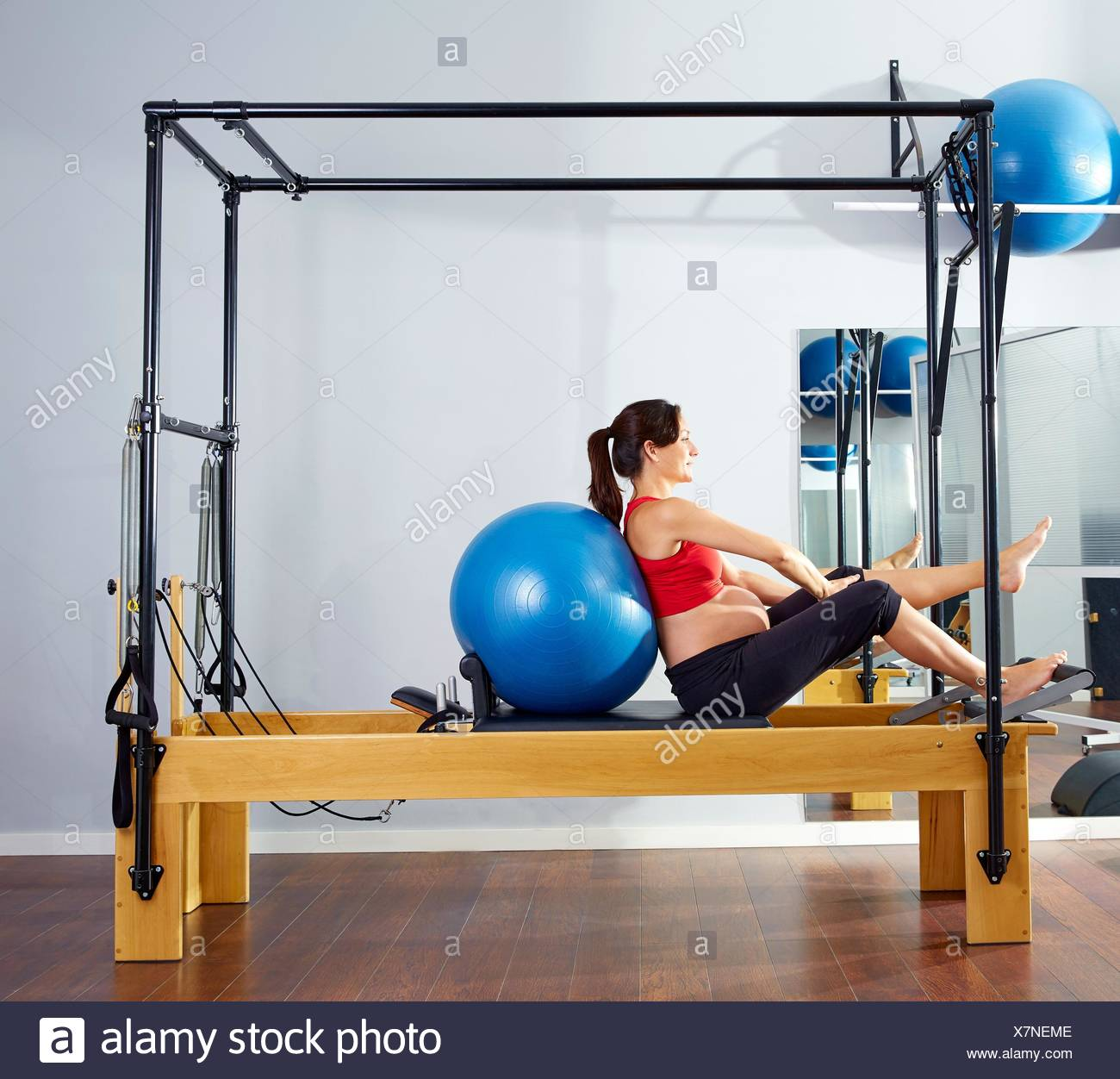 pregnant woman pilates reformer fitball exercise workout at gym. - Stock Image