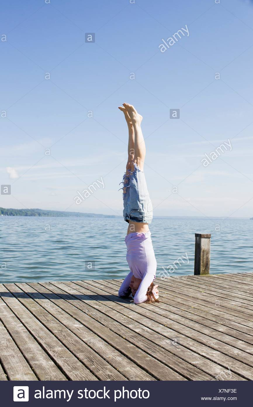Mature woman on pier by ocean balancing on head - Stock Image